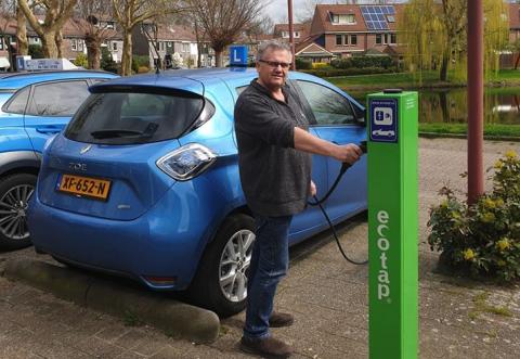 Rijschoolhouder Wim van Dijk bij zijn elektrische lesauto, Renault ZOE
